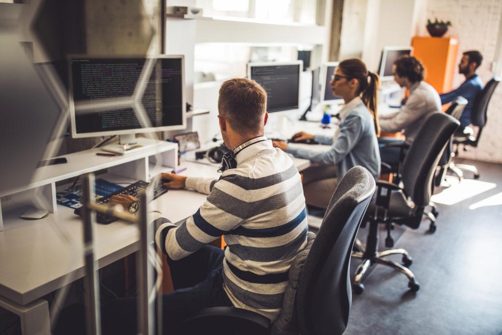 computer programmers working on desktop pcs in office
